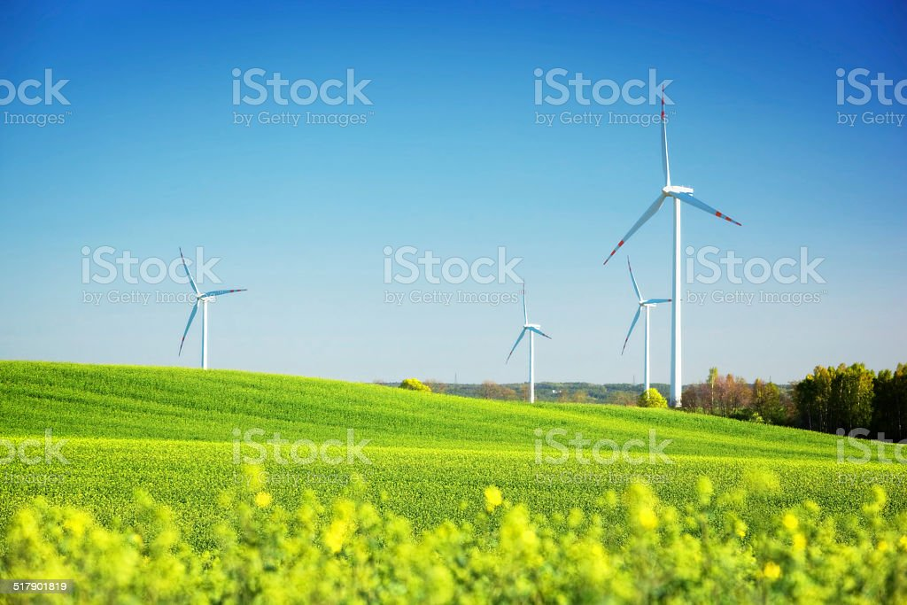 Wind turbines on spring field. Alternative, clean and natural energy stock photo