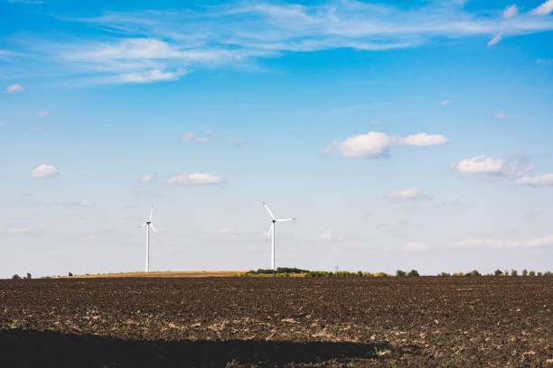 Wind turbines on the horizon behind the field against the blue sky. Industrial landscapes of Ukraine. stock photo