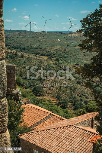 Wind turbines for electric power generation over hilly landscape and rooftops, seen by stone crenel at Sortelha. One of the most astonishing and well preserved medieval villages in all Portugal.