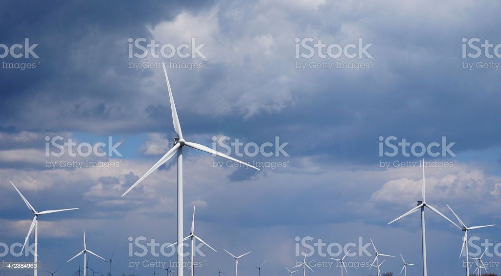 wind turbines White wind turbines against gloomy sky 2015 Stock Photo