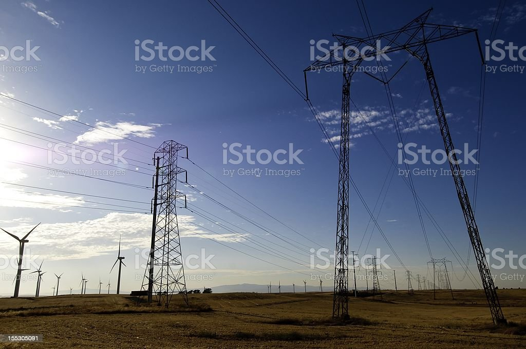 Wind Turbines Power Grid Power lines running through the Wind Farm with blue sky as background. Environmental Conservation Stock Photo