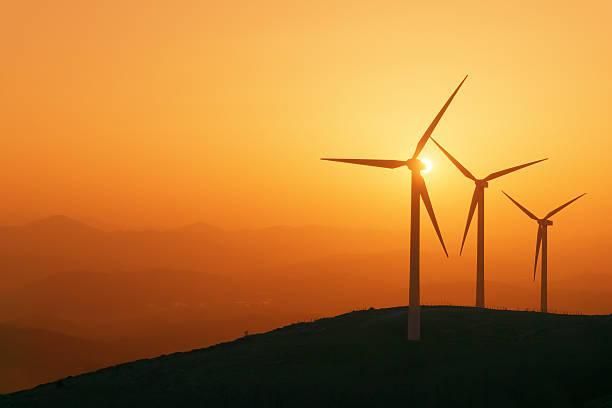 Turbinas de viento en la puesta de sol sobre las montañas de silhouette - foto de stock