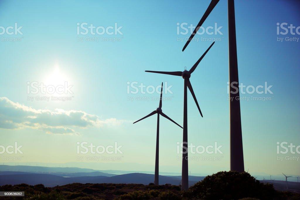 Wind turbines silhouette on mountain stock photo