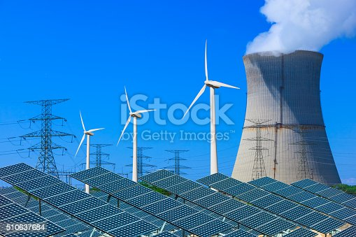 Solar panels with wind turbines in the foreground leading back to a atomic energy plant against a clear blue sky