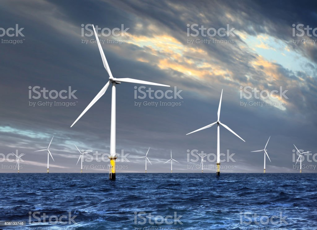 wind turbines under cloud sky stock photo