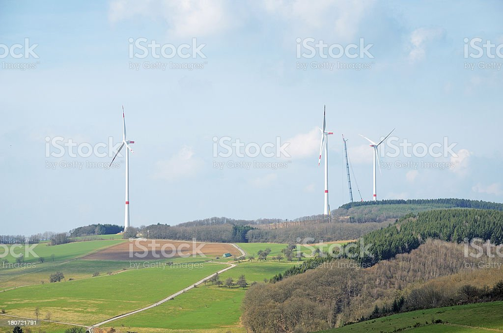 Wind turbines with crane on hilly landscape royalty-free stock photo