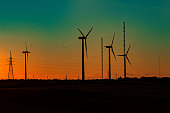 Wind turbines with orange green sunset and flock of birds.\