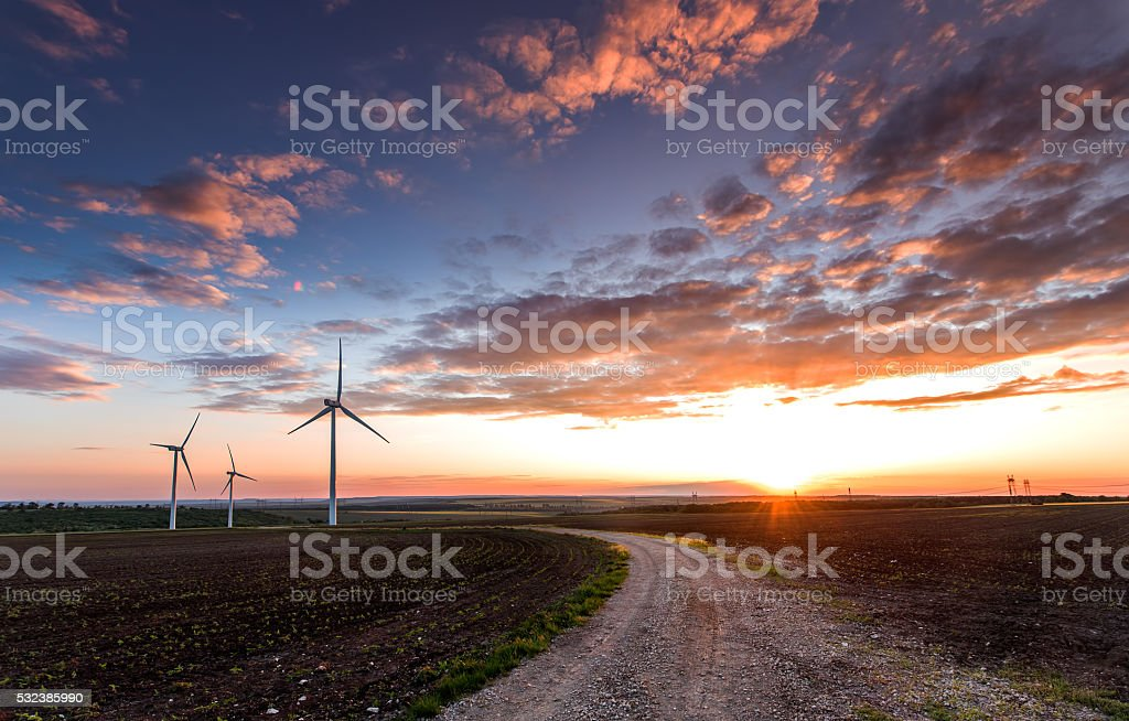 Wind turbines with power line in the sunset! stock photo