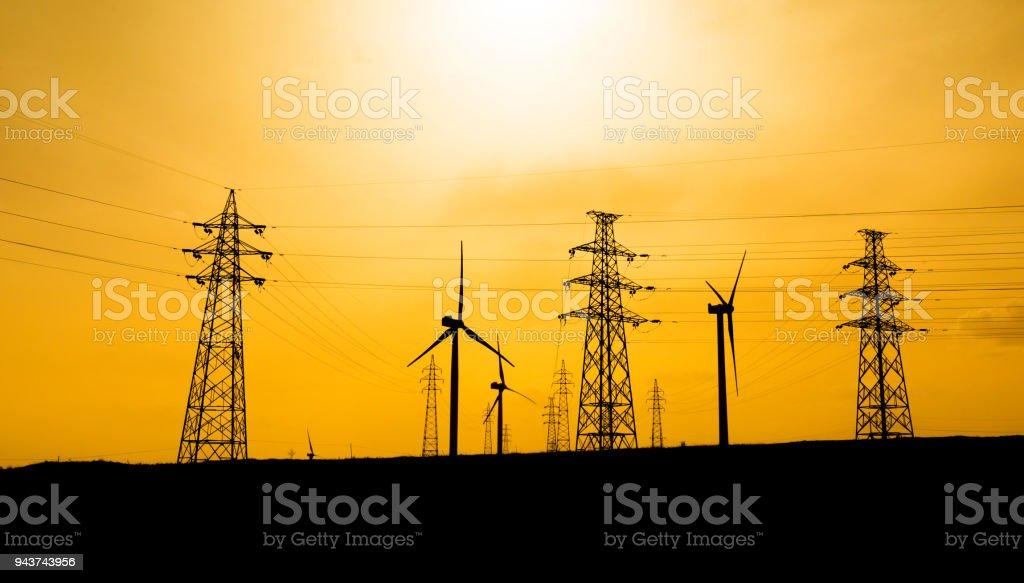 Windkraftanlagen mit Pylon bei Sonnenuntergang – Foto