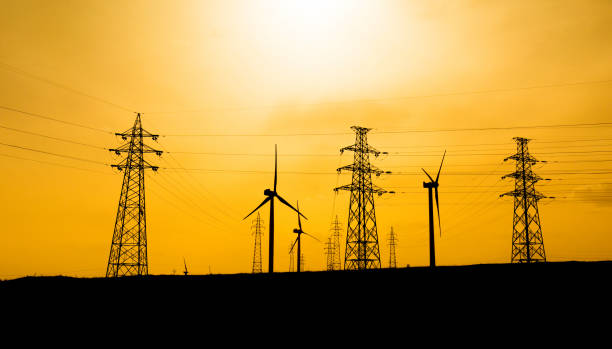 wind turbines with pylon at sunset - power in nature stock photos and pictures