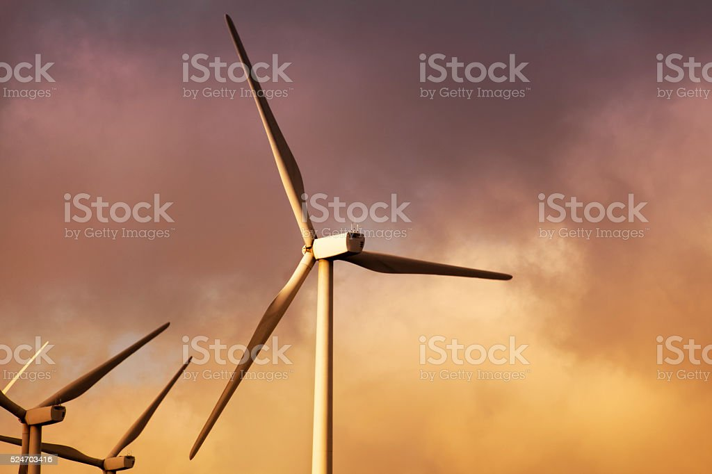 Wind turbines with sunset background, sustainable energy, environmental conservation. stock photo