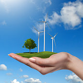 Wind turbines on meadow with tree holds in womans hand against blue sky and clouds. Green energy concept