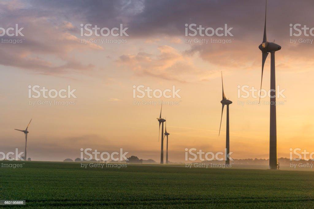 wind wheels at sunrise and fog with dark clouds Lizenzfreies stock-foto