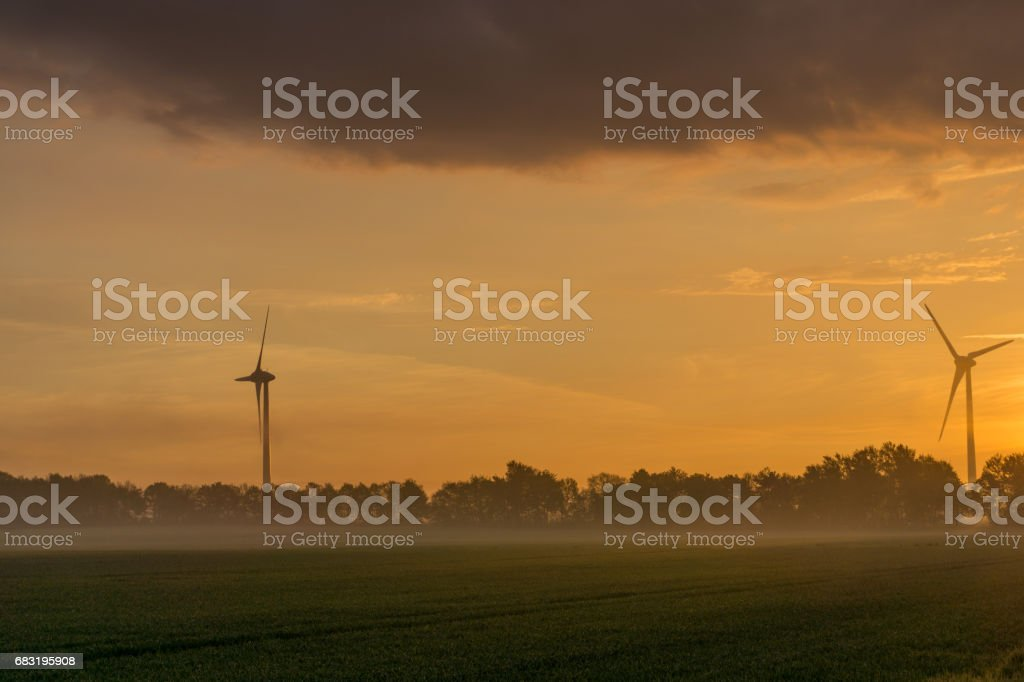 wind wheels at sunrise and fog with dark clouds 免版稅 stock photo