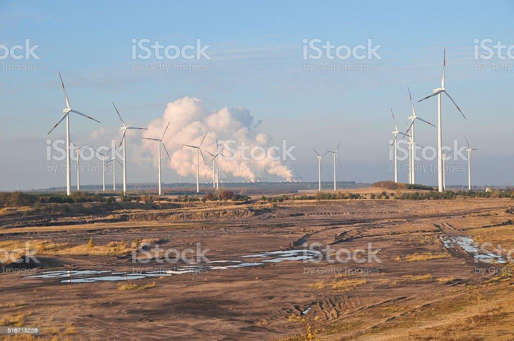 Wind-Räder auf Bergbau Feld, dem Kraftwerk im Hintergrund - Lizenzfrei Abenddämmerung Stock-Foto