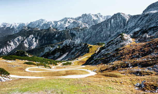 Winding alpine road to valley - Bavarian alps Beautiful alpine path to the valley in the area of Garmisch Partenkirchen - Bavaria Germany bavarian alps stock pictures, royalty-free photos & images