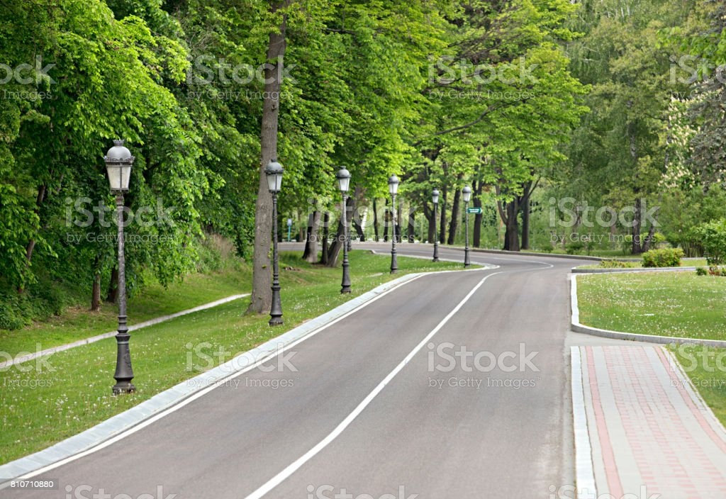 A winding asphalt road and a sidewalk for pedestrians through the park with a number of beautiful vintage lamps stock photo