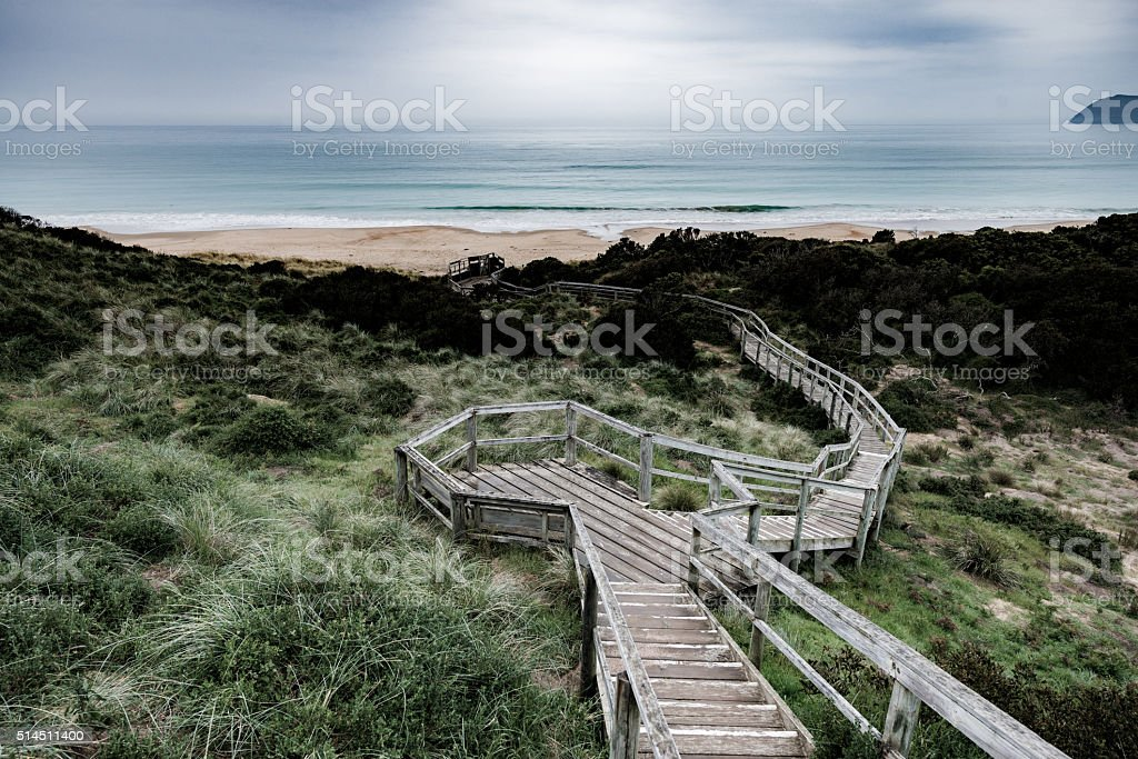 Winding Boardwalk Leads Over Scrubland and Dunes to Distant Beach stock photo