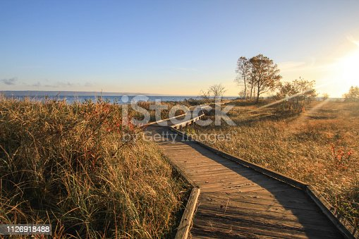 832047798 istock photo Winding Boardwalk Path Through Dune Grass On Lake Superior 1126918488