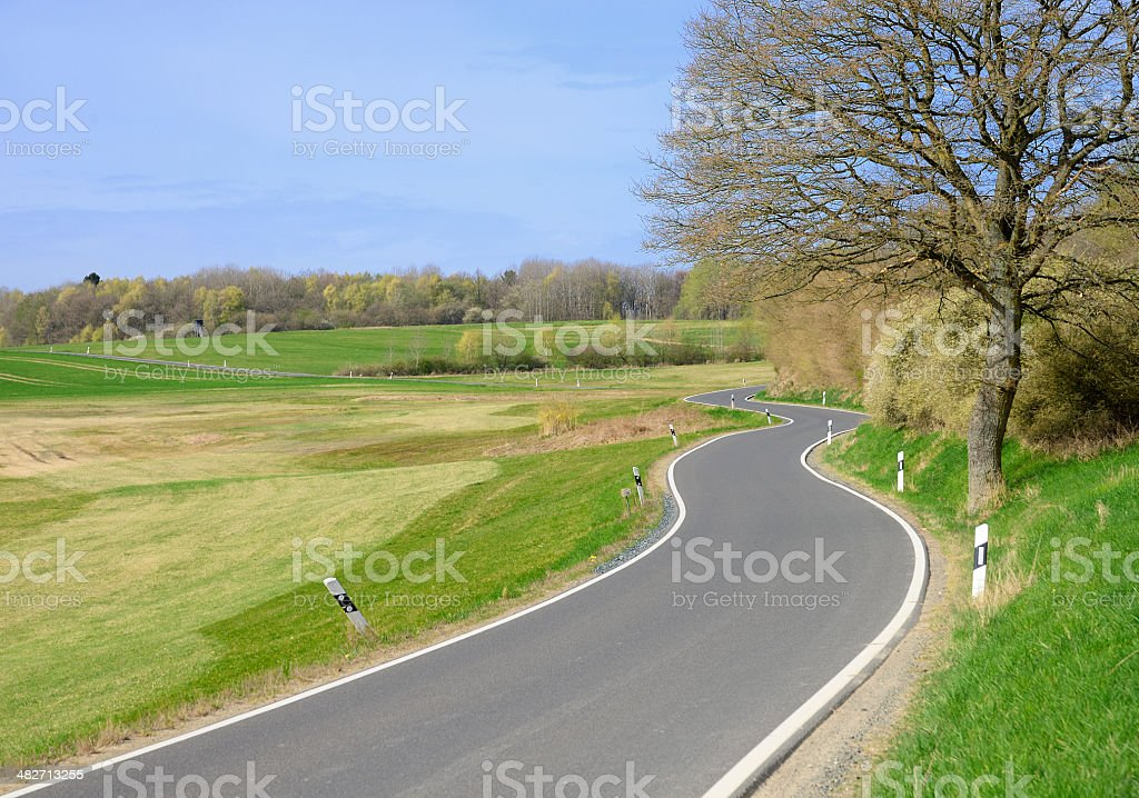 Winding country road through meadow royalty-free stock photo