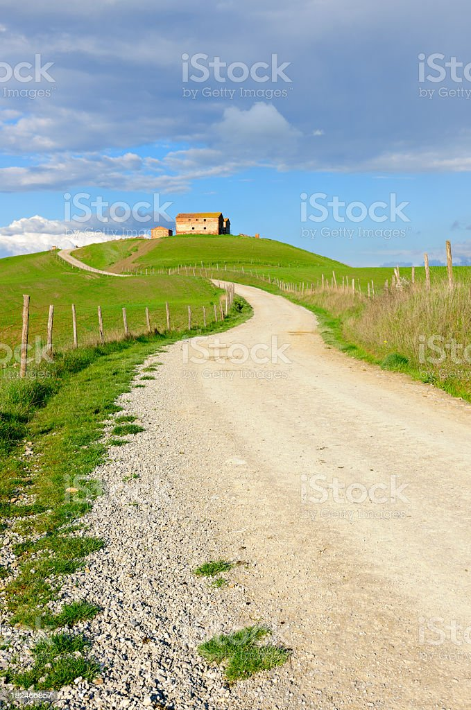 Winding Dusty Farm Road in Rural Tuscany Landscape royalty-free stock photo