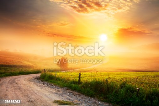 istock Winding Farm Road through Foggy Landscape 158636263