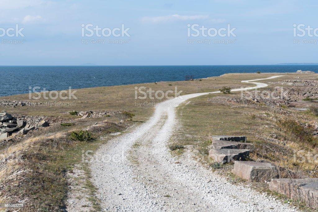 Winding gravel road in a coastal landscape stock photo