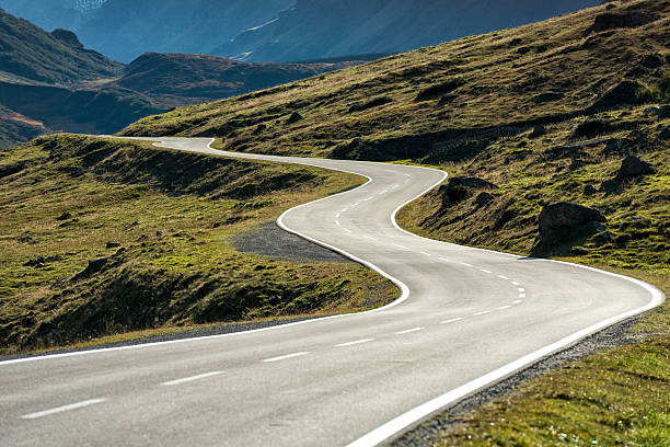winding mountain road without cars DSLR photo of a landscape with a winding mountain road with many curves in the austrian alps leading from Galtuer in Tyrol above the Silvretta Bielerhoehe to Vorarlberg. Nobody is on the street at this sunny day. steep stock pictures, royalty-free photos & images