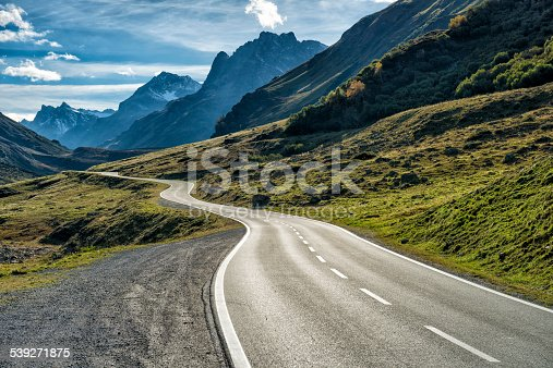 DSLR photo of a landscape with a winding mountain road with many curves in the austrian alps leading from Galtuer in Tyrol above the Silvretta Bielerhoehe to Vorarlberg. Nobody is on the street at this sunny day.