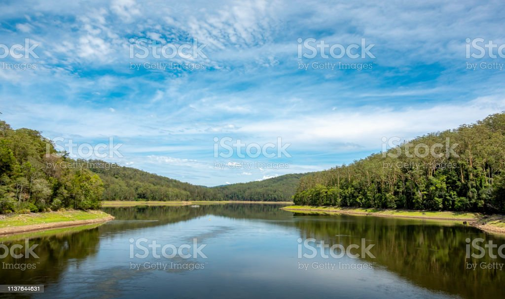 Winding river flanked by natural woodlands on the both sides stock photo