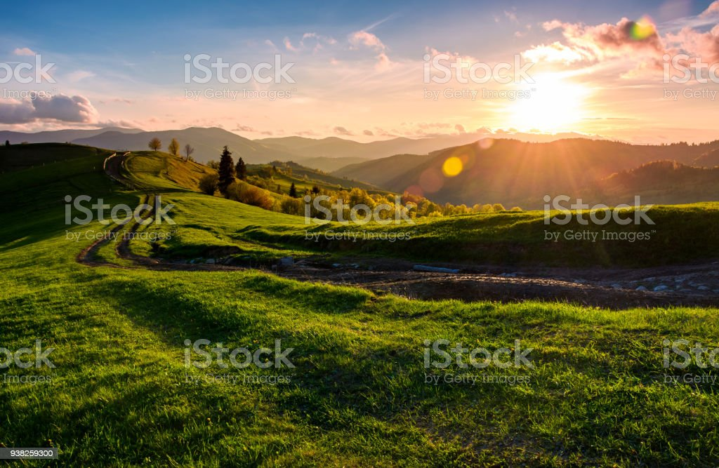 winding road along the grassy rural hill at sunset stock photo