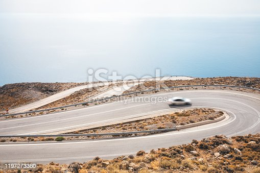 Car driving on a winding mountain road (south Chania region, Crete, Greece).