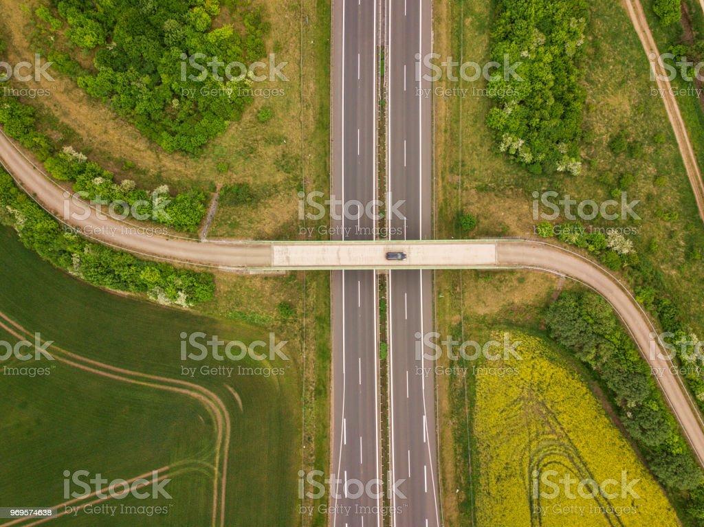 A car on winding road crossing a huge road between fields,...