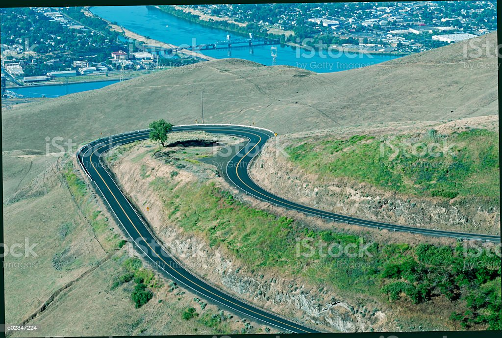 Winding road from plateau to town in Idaho stock photo