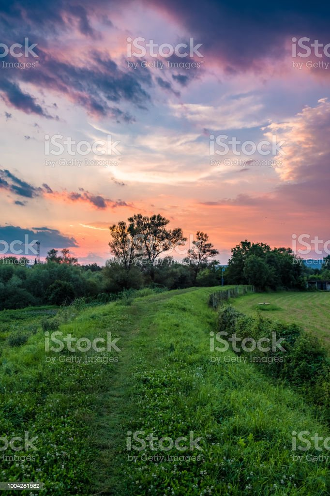 Winding road going through the field with colorful sunset sky above stock photo