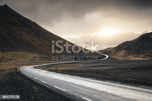 Winding road in Iceland illuminated by the sunlight.