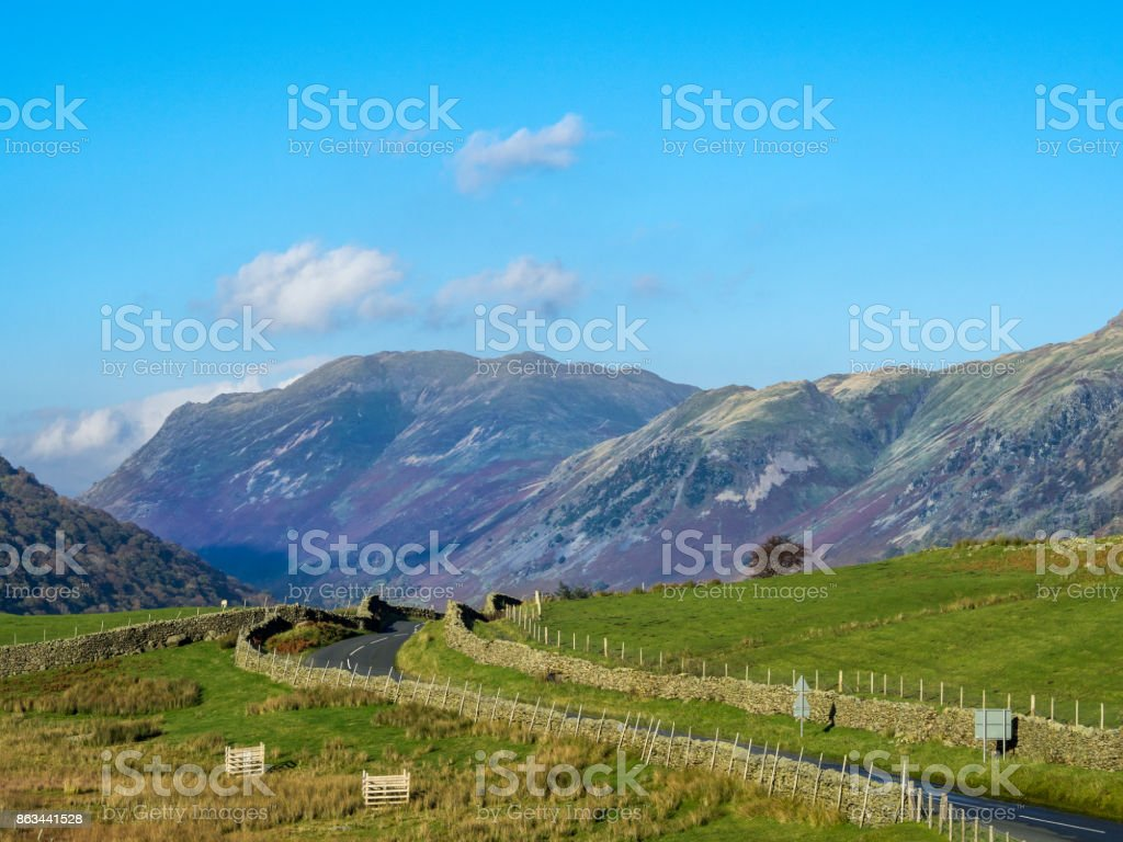 Winding Road in Lake District with stone walls and mountains in distance stock photo