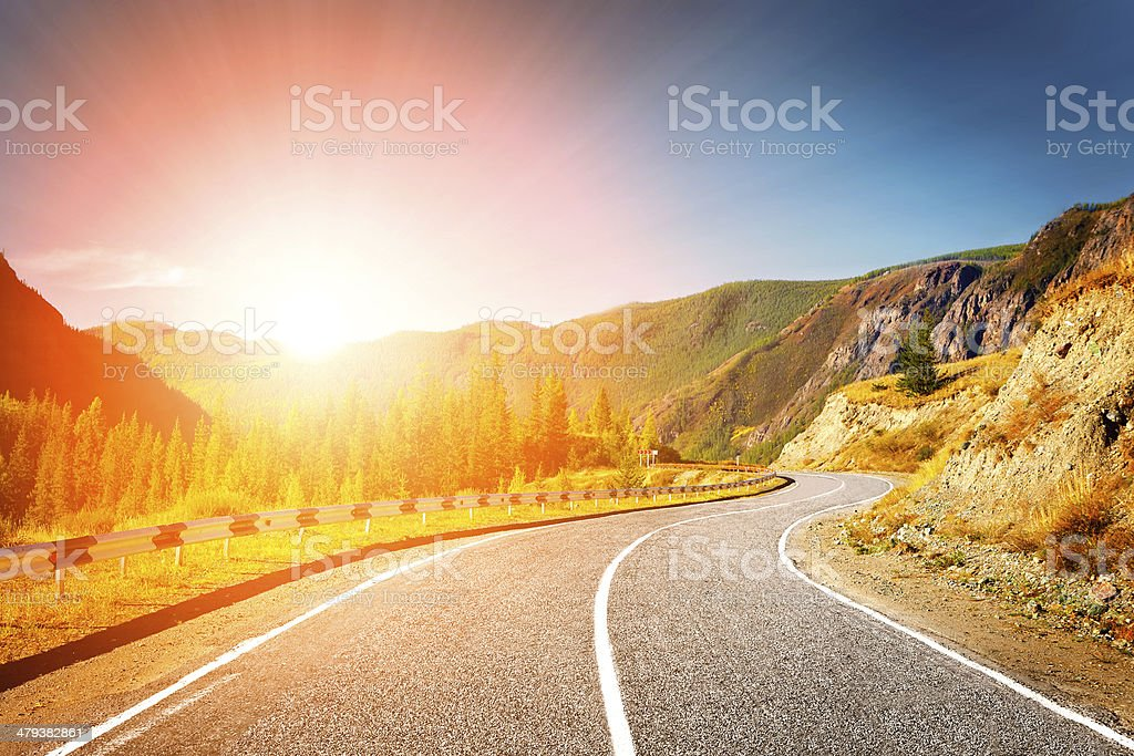 Winding road in mountain valley at sunset stock photo