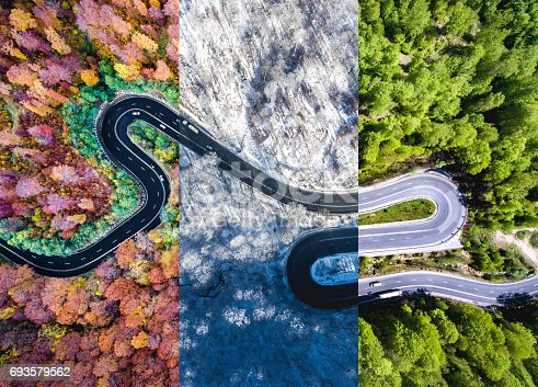 istock Winding road in the forest. Autumn, summer and winter time colage. Top down aerial view from a drone. 693579562