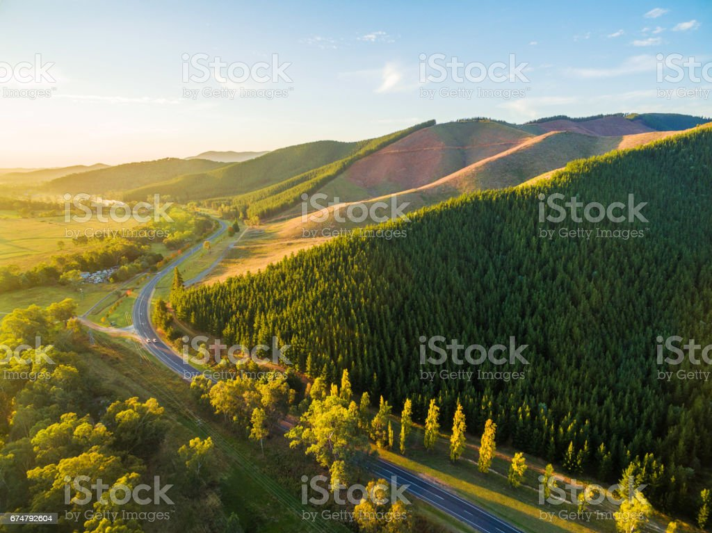 Winding road passing through beautiful Australian countryside at sunset stock photo