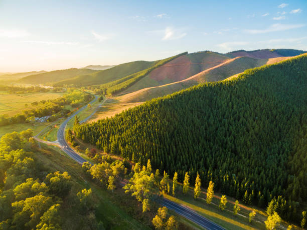 Winding road passing through beautiful Australian countryside at sunset stock photo