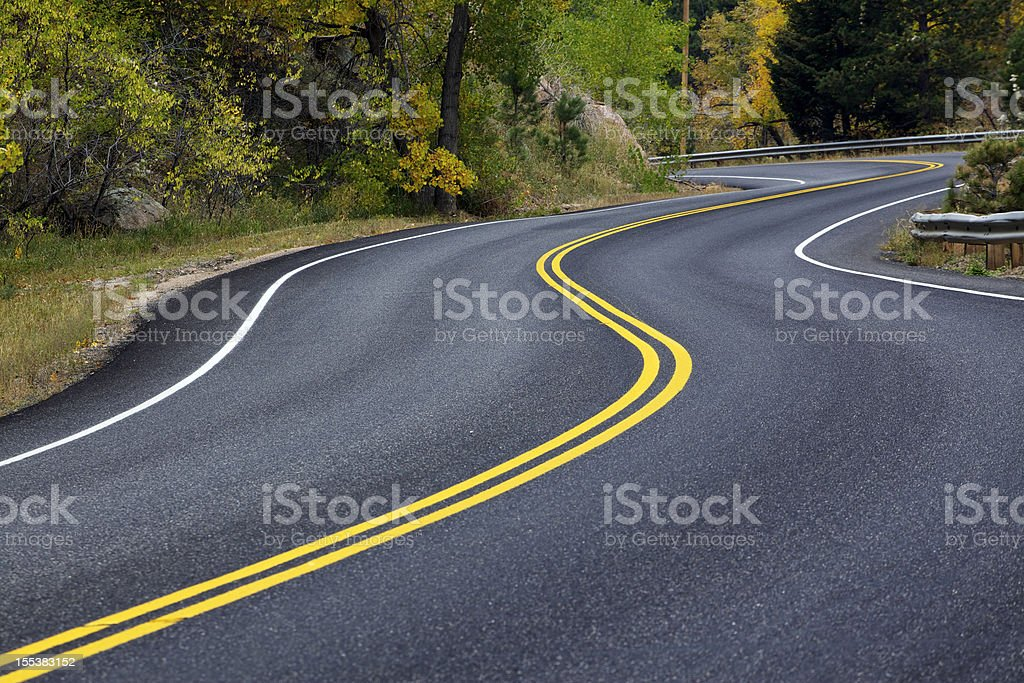 Winding Road through Canyon full of Fall Colors in Colorado stock photo