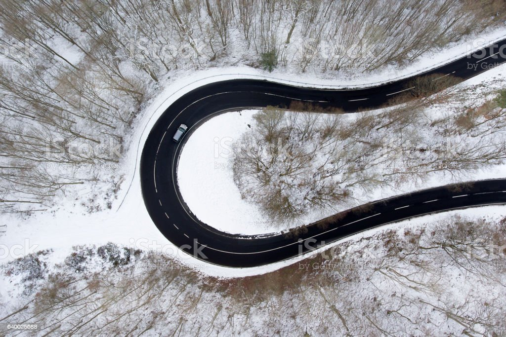 Winding road through the wintery forest - aerial view stock photo