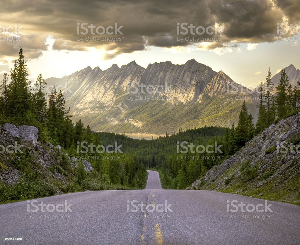 Winding road towards distant mountains at beautiful sunrise stock photo