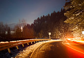 winding road with car light trails at night