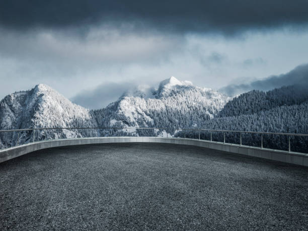 winding snowy road leading towards snow mountains stock photo