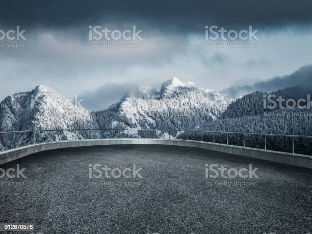 Photo of winding snowy road leading towards snow mountains