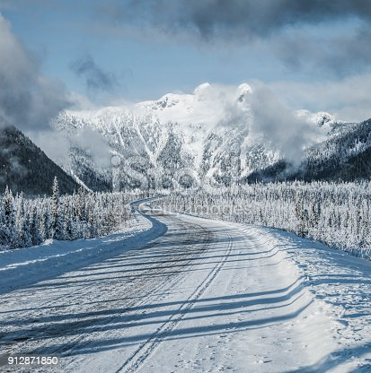 istock winding snowy road leading towards snow mountains 912871850