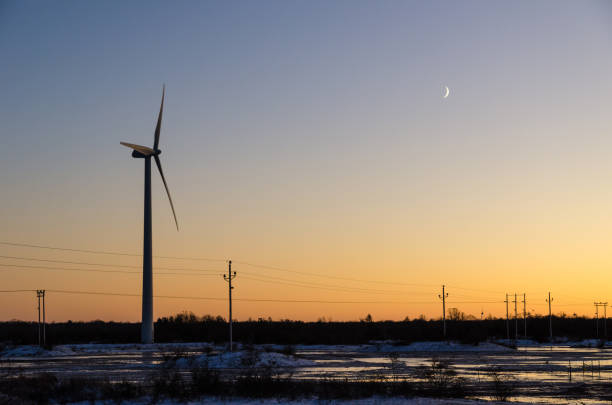 Windmill and power lines by sunset stock photo