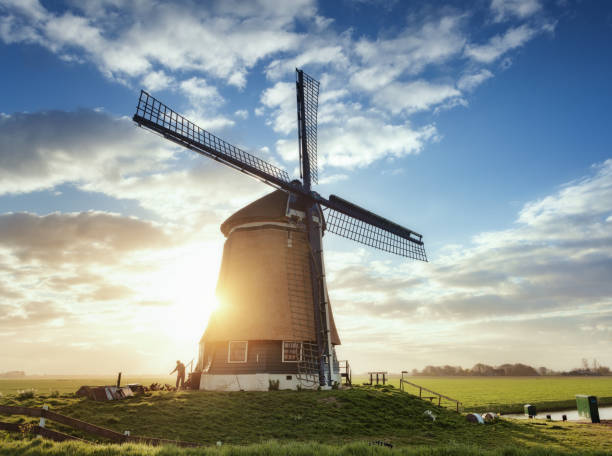 windmill and silhouette of a man at sunrise in netherlands - netherlands stock photos and pictures
